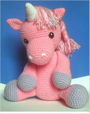 Crocheted Pink Unicorn sitting on a light green surface in front of a blue background