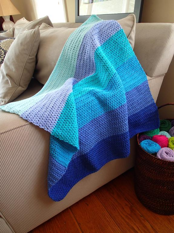 Crocheted blue blanket in different clue shaded on a beige sofa in a living room with a yarn basket