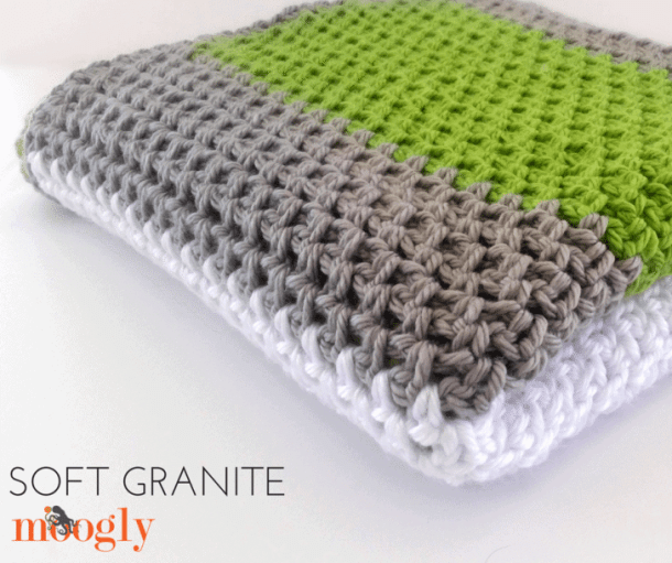 Crocheted Green, Grey, White Blanket on a white surface