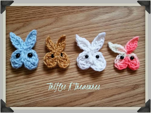Four colorful East Bunny Face Appliques with black eyes laying on a wooden counter top.