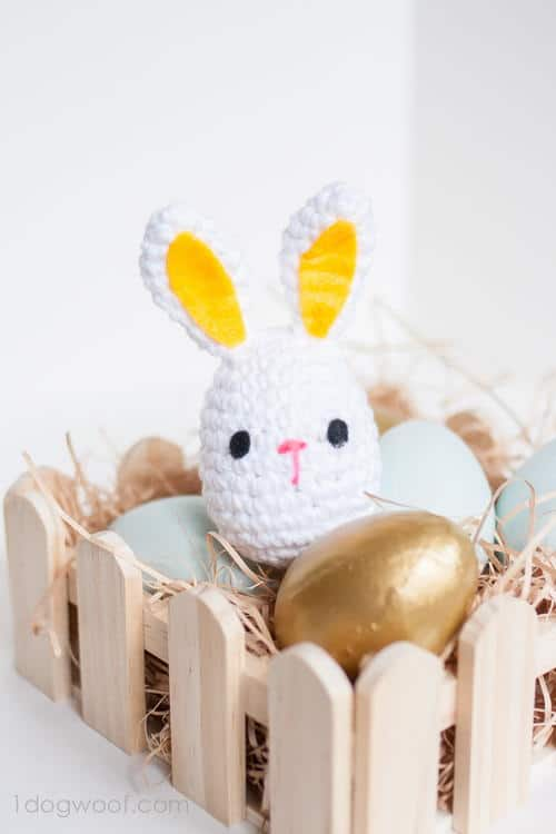 An Easter Bunny as an egg sitting in a wood basket of eggs.