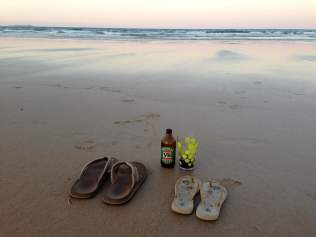 Flip flops and beer on the beach at sunset on Goolawah Beach, Australia