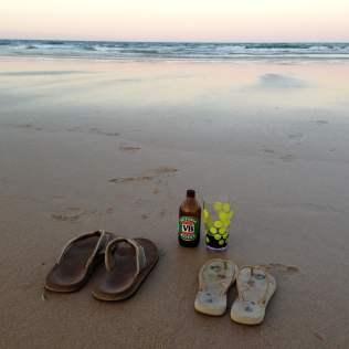 Flip flops and beer on the beach at sunset on Goolawah Beach, Australia
