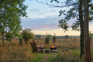 Matt sat by the fire pit while glamping in a shepherd's hut at Warmwell House in Dorset.