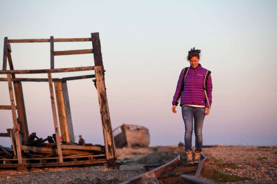 An image of me walking along the old railway line on Dungeness beach wearing West Beach Downhill jacket.