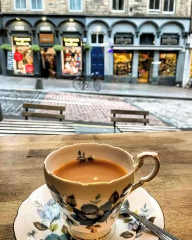 An image of a cup of tea with a view behind of shops on the Royal Mile in Edinburgh.