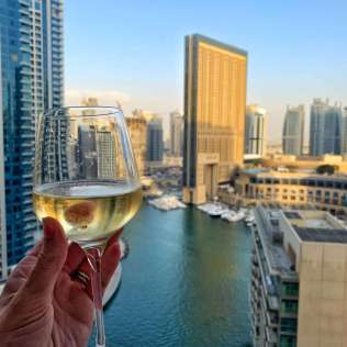 A glass of wine and the view behind of Dubai Marina