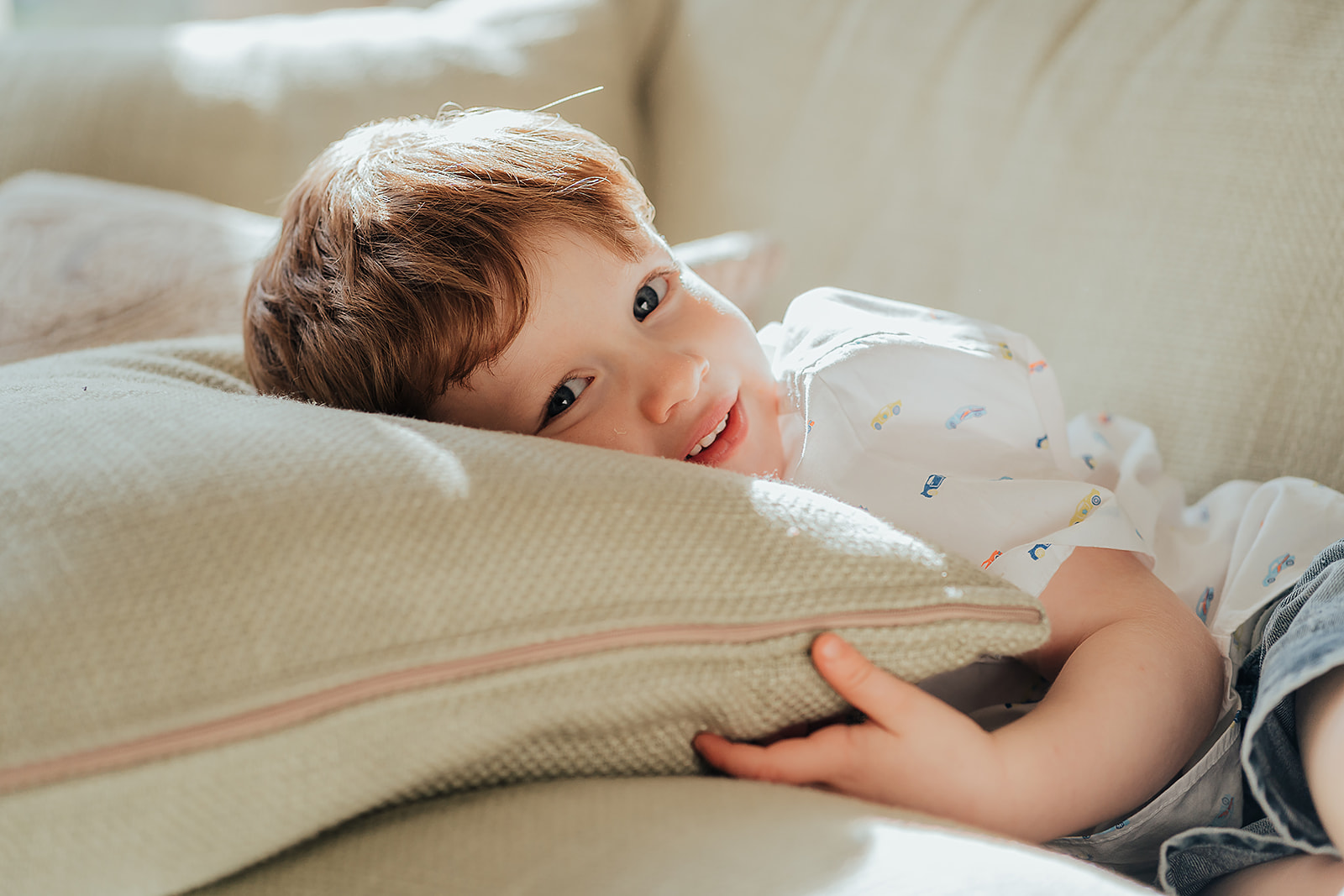 little boy lying down on a sofa, head on a pillow