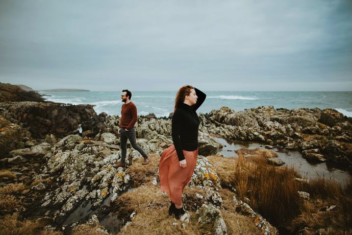 Couple standing on rocks by the coastline