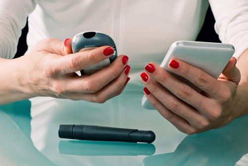 A woman holding a blood glucose test meter and a smartphone used to log results. On the table is a finger-prick tool, called a lancet, which is used to draw a drop of blood.