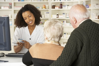 Couple talking with a pharmacist.