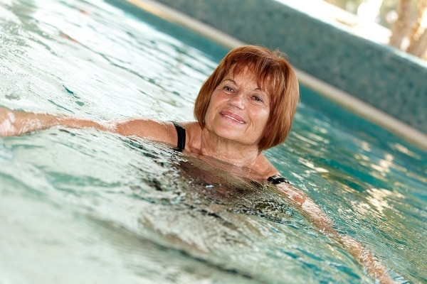 Photo of a middle aged woman swimming indoors - La diabetes Tipos y prevención de enfermedad