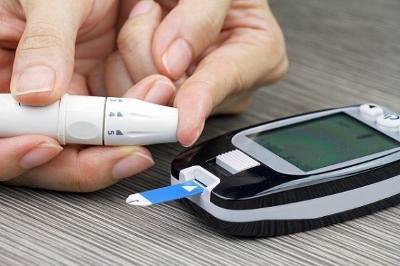 Photo of a woman's hands and a blood glucose meter. She is pricking her fingertup with a lancet.