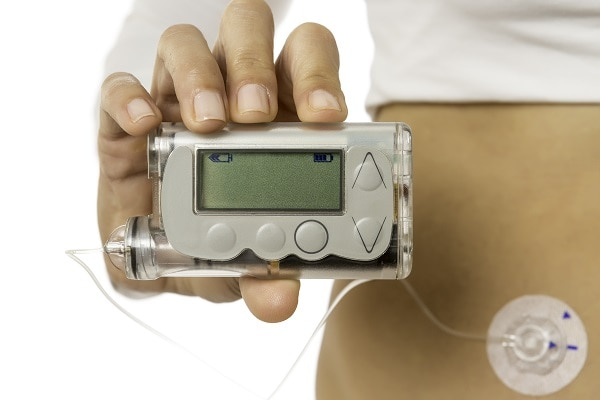 Photo of a woman holding a blood glucose meter - La diabetes Tipos y prevención de enfermedad