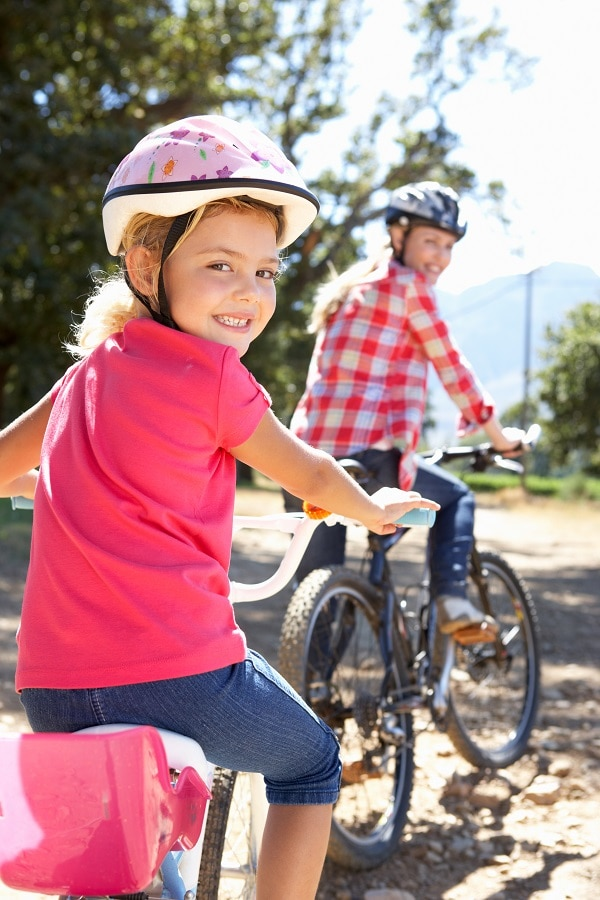 Photo of mother and young daughter riding bikes - La diabetes Tipos y prevención de enfermedad