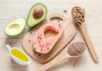 Foto de aguacate, salmón, nueces, semillas y aceite de oliva.