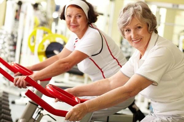 Foto de dos mujeres de mediana edad sonriente en bicicletas de ejercicio