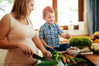 A pregnant woman chopping vegetables in the kitchen with her young son.
