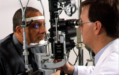 Eye doctor examines a man's eyes for signs of eye disease during a full, yearly eye exam.