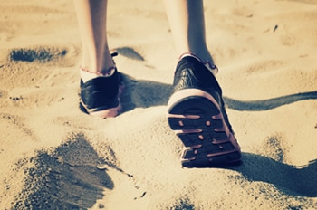 Photo of someone's feet wearing shoes and walking on the sand.