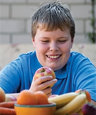 Overweight boy with bowl of fruit.