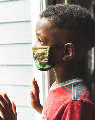 child with COVID-19 face mask looking out the window