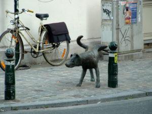 Standbeeld van hond, plassend tegen een echt paaltje. Copyright natasa2004.