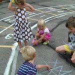 Kinderen leren elkaar op de speelplaats de spelregels van het spel boter, kaas en eieren. Copyright foto Ned Horton.