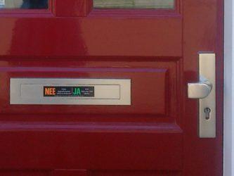 Deel van voordeur met brievenbus met nee/ja sticker en deurknop