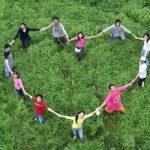 Mensen staan in een hartvormige kring op een grasveld. Copyright foto: Kung Kung