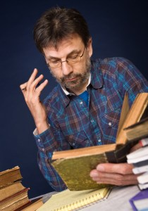 Mature man reading old book surrounded by heaps of books, uitvinder? copyright foto: Mikhail Lavrenov