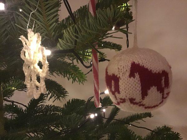 Gebreide Kerstbal en gehaakte sneeuwster In kerstboom