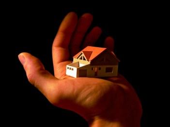 Een miniatuurmodel van een huis op een hand. Copyright: Viktors Kozers