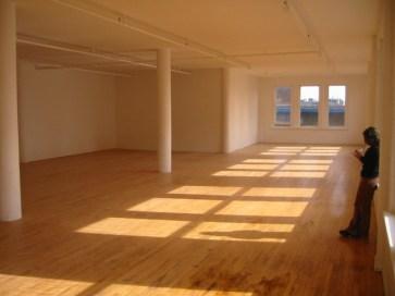 Lege open ruimte met witte muren, ramen, pilaren en ene houten vloer. Copyright Christopher Thiemet