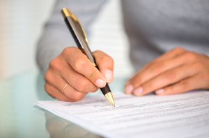 Woman at office desk signing a contract with shallow focus on si