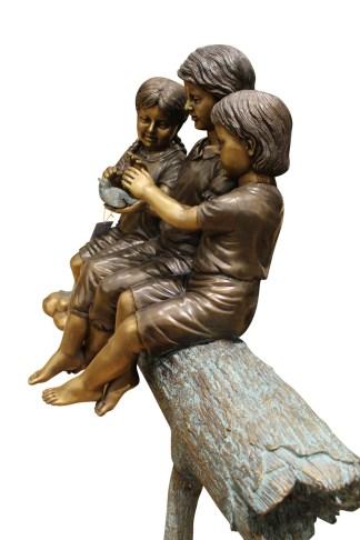 """Three Children On Log Holding Bird Bronze Statue -  Size: 55""""L x 18""""W x 38""""H."""