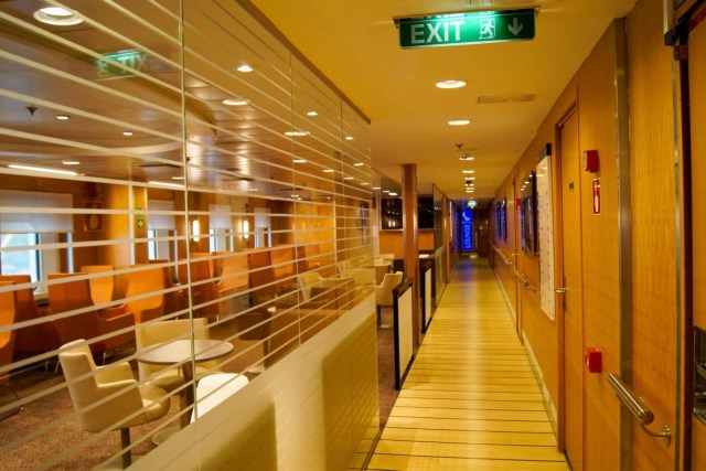 This corridor at the rear of the bar/coffee house leads to a dedicated reclining seat lounge for commercial drivers (previously a second cinema) and the red stairs (which is a bit hidden to the right and round a corner). The remaining cinema occupies the same space on the other side of the ship. Copyright © Steven Tarbox.