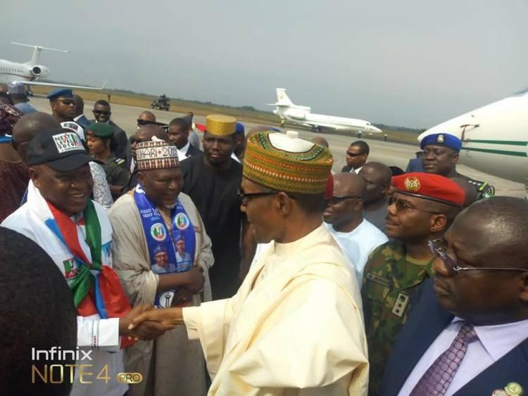 Olorogun O'tega Emerhor in a handshake with President Buhari during the president visit to Warri on Thursday.