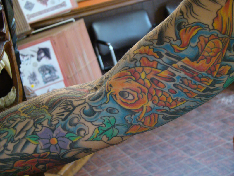This is an oldschool full sleeve tattoo featuring koi fish, dragons,