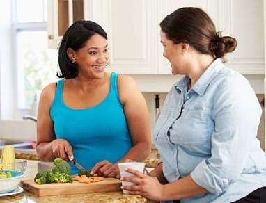 Two overweight women preparing vegetables in the kitchen