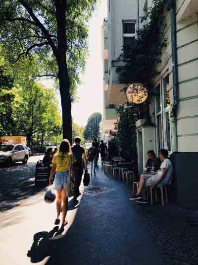 People walking and sitting outside, on the sidewalk past Populus Cafe in Berlin.