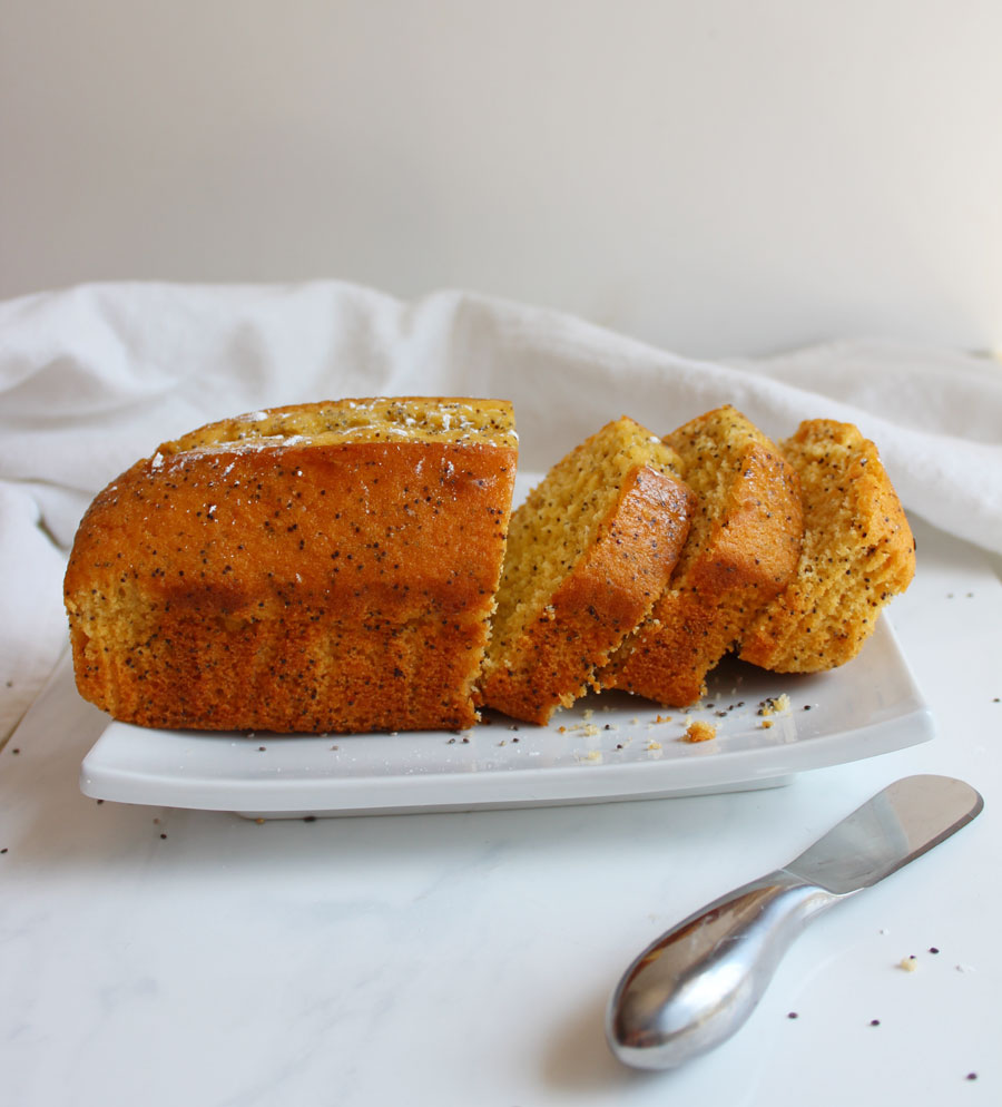 Large Lemon Poppy seed Loaf cut into slices on white plate- Vegan and Gluten Free