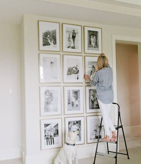 DIY photo gallery wall idea to help you design the best piece of art in your home! Black and white photos, large, gold frames, full wall - #goldframes #largegallerywall #blackandwhitephotos || Nikki's Plate