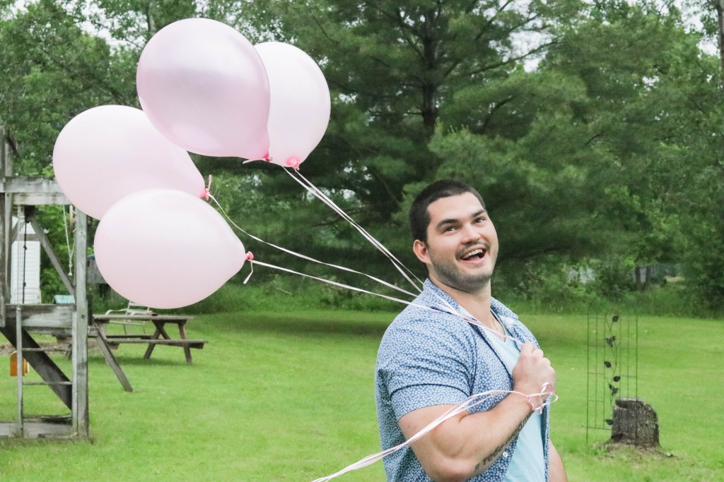 Gender Reveal Party - brother holding pink balloons