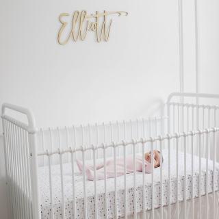 Elliott's White Vintage Crib; White walls, cursive name sign on wall, wainscotting, bright white baby girl room. #babygirlnursery || Nikki's Plate