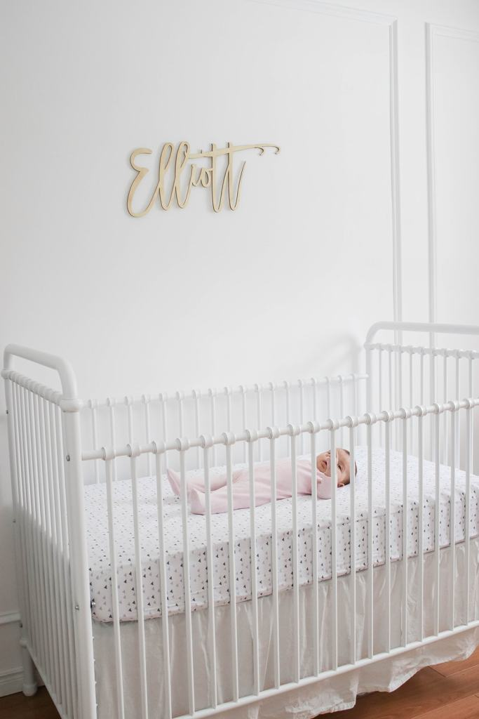 Elliott's White Vintage Crib; White walls, cursive name sign on wall, wainscotting, bright white baby girl room. #babygirlnursery || Nikki's Plate