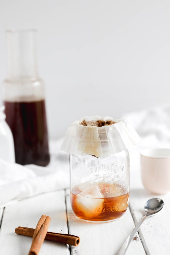 Overnight Cinnamon Cold Brew Coffee - coffee filter over mason jar to filter out coffee grinds. almond milk beside {vegan}