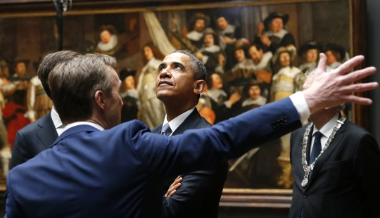 U.S. President Barack Obama, center, listens to Rijksmuseum director Wim Pijbes, seen from the back, in front of Dutch master Rembrandt's The Night Watch painting during a visit to the Rijksmuseum in Amsterdam, Netherlands, Monday, March 24, 2014. Obama will attend the two-day Nuclear Security Summit in The Hague. (AP Photo/Frank Augstein)