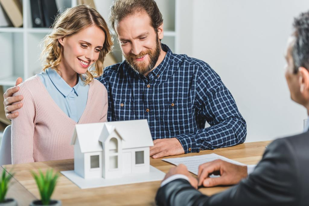 portrait of couple having meeting with realtor in real estate agency office