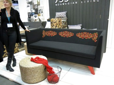 Grey sofa with red legs and norwegian patterns on the backrest.
